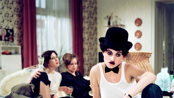 Drei Frauen in einem Bett. Eina e als Charlie Chaplin verkleidet. Ute Lubosch (l.), Marie Gruber (m.) und Silke Matthias