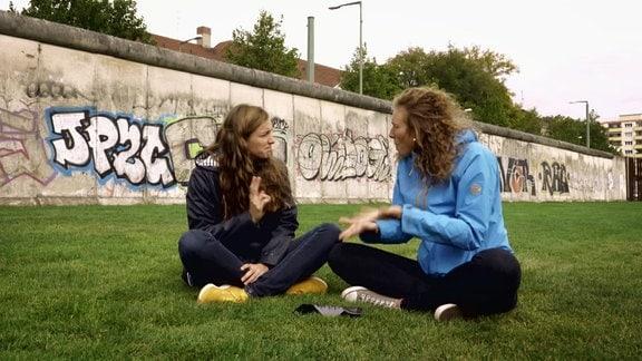 """Zwei gehörlose Frauen sitzen an einem Stück der """"Mauer"""" auf einer Wiese und unterhalten sich in Gebärdensprache"""