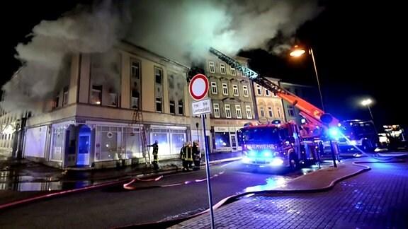 Die Feuerwehr löscht ein brennendes Haus.