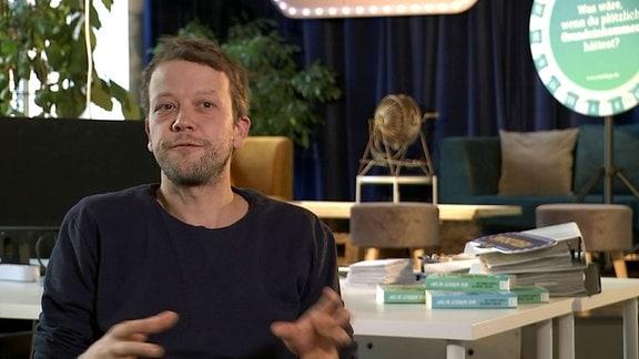 Michael Bohmeyersitzt vor einem Tisch und blickt in die Kamera
