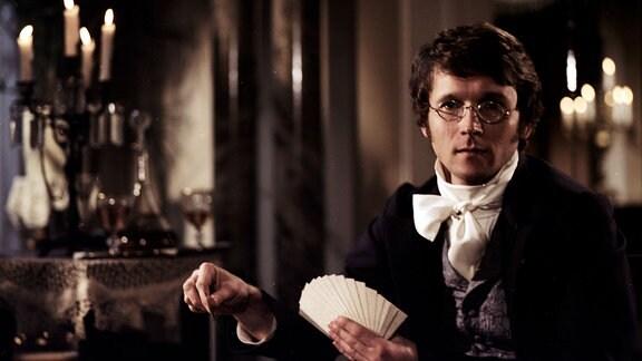 Frank Lienert (Carl Maria von Weber) hält eine Reihe Karten in der Hand udn schaut ernst in die Kamera
