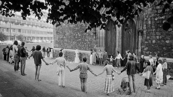 Archivbild: eineMenschenkette vor einer Kirche
