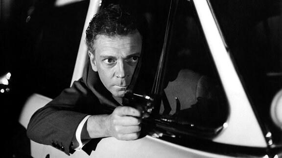 Ein Mann zielt mit einer Pistole aus dem Fenster seines Autos nach vorn, sein Blick ist angespannt.