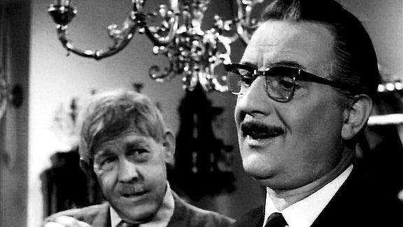Zwei Männer unterhalten sich in einem Innenraum. Beide lächeln. Im Hintergrund ist ein Kronleuchter zu sehen.