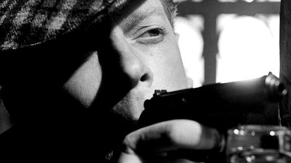 Ein Mann mit karierter Schiebermütze visiert mit lässigem Blick ein nicht sichtbares Ziel mit seiner Pistole an.