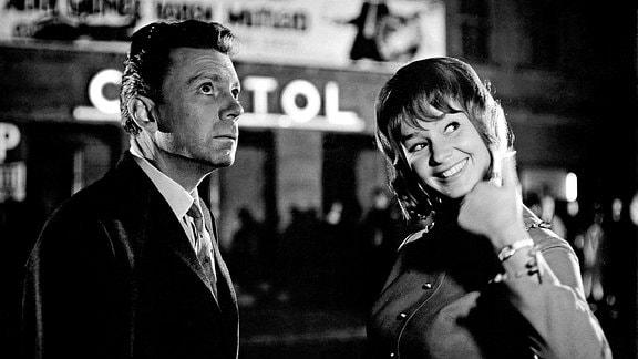 Ein Mann und eine Frau auf einer belebten Straße. Er schaut angespannt nach oben, sie schaut fröhlich nach rechts und zeigt ihren Daumen nach oben.