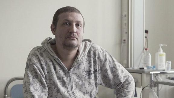 Ein Mann sitzt in einem Krankenzimmer.
