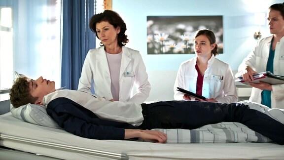 Drei Ärztinnen in weißem Kittel stehen an einem Krankenbett mit einem männlichen Patienten.