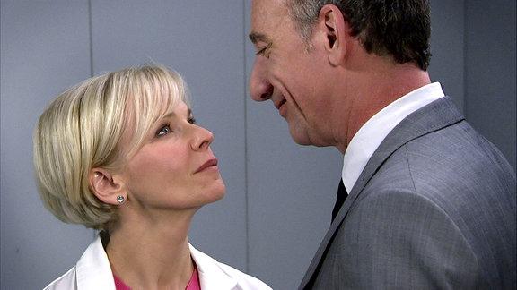 Frau Dr. Kathrin Globisch (Andrea Kathrin Loewig) schaut zu Alexander Weber (Heio von Stetten) hinauf, der sie anlächelt.