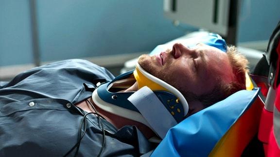 Mann mit Halskrause liegt auf einem Krankenbett