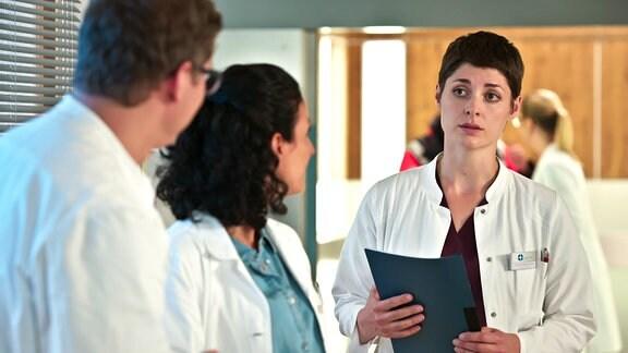 Zwei Ärztinnen und ein Arzt unterhalten sich.