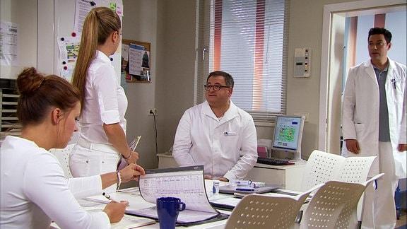 Schwester Julia (Sarah Tkotsch), Pflegedienstleiterin Arzu Ritter (Arzu Bazman), Pfleger Hans-Peter (Michael Trischan) und Dr. Philipp Brentano (Thomas Koch) unterhalten sich.