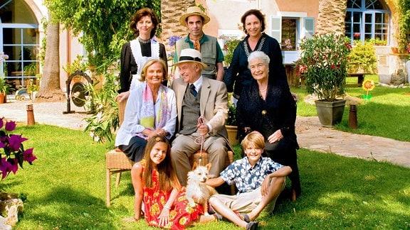 Ein Familienfoto von acht Personen auf einer grünen Wiese
