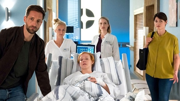 Julia Berger (Mirka Pigulla, 2.v.r.) und Theresa Koshka (Katharina Nesytowa, r.) sorgen sich um die Föten von Lisa Meininger (Nina Rausch, M.), die Kinderwunschpatientin wurde mit einem Schienbeinbruch von ihrem Mann Lars (Dominik Maringer, l., mit Komparsin) ins JTK gebracht.
