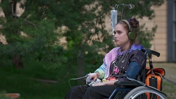 Ein junges Mädchen sitzt im Hof der Klinik in ihrem Rollstul und hört Musik