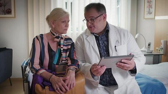 Zusammen mit einer Patientin wertet ein Pfleger Röntgenbilder aus