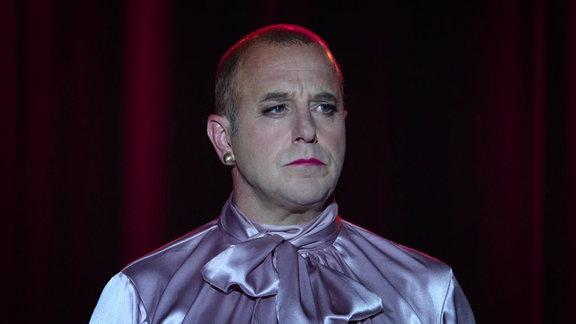 Ein Mann in Frauenkleidung steht auf einer Bühne
