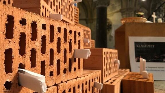 In der Leipziger Peterskirche stecken Zettel in den Löchern von Blockziegeln