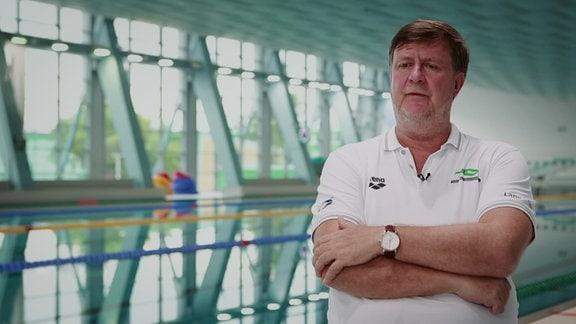 Ein Trainer steht in einer Schwimmhalle am Beckenrand
