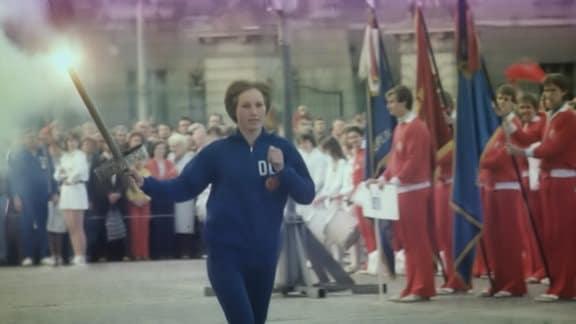 Eine Sportlerin der DDR trägt das olympische Feuer