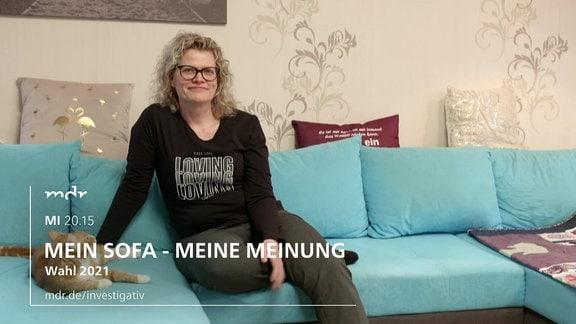 Eine blonde Frau sitzt auf einem Sofa