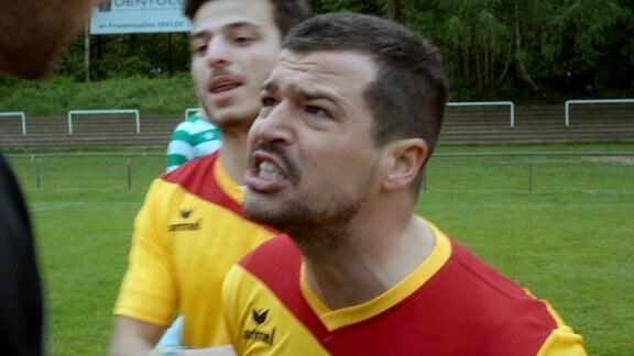 Der Fußballer Emre Yilmaz bekommt nach einem Foul vom Schiedsrichter die Rote Karte und ist stocksauer.