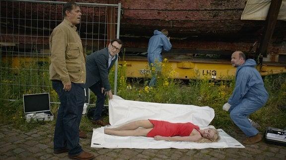 Eine junge Frau in einem roten Kleid wird tot aufgefunden