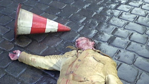Toter Mann auf regennasser Straße.
