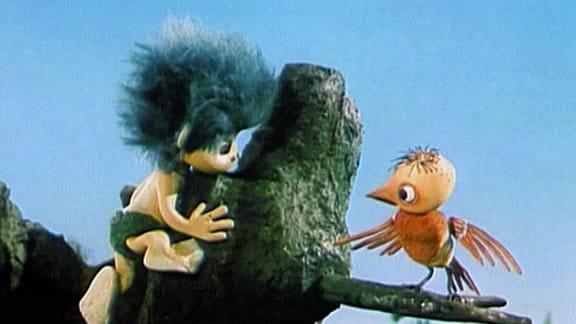 Der Plumps klettert auf einen Baum zu einem Vogel.