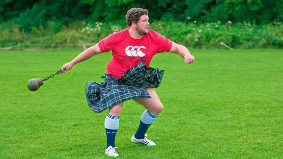 Ein Mann im Kilt trainiert für die Highland Games