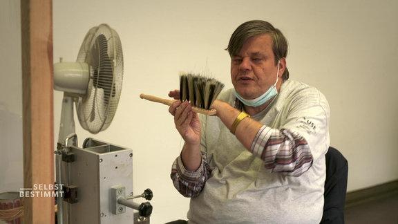 Ein Mensch mit Behinderung in einer Werkstatt.