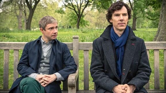 Sherlock (Benedict Cumberbatch, re.) und John Watson (Martin Freeman) sitzen auf einer Bank.