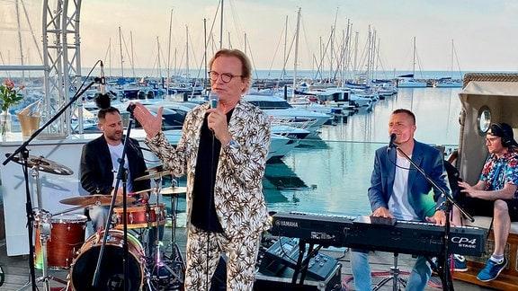 Wolfgang Lippert, Kühlungsborn. Eine Person in Anzug mit Palmenmotiv spricht in ein Mikrofon, hinter ihr sitzt eine Person am Schlagzeug und eine Person an einem Keyboard. Im Hintergrund der Hafen von Kühlungsborn.