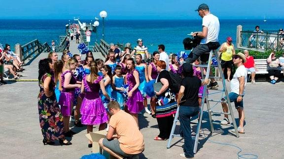 Kühlungsborn - Prinzessinnen-Garde: Samba de Kübo. Eine Gruppe mit ungefähr zwei Dutzend Personen in schwarz-violetten oder blauen Kleidern steht auf einer Strandpromenade, im Hintergrund das Meer.