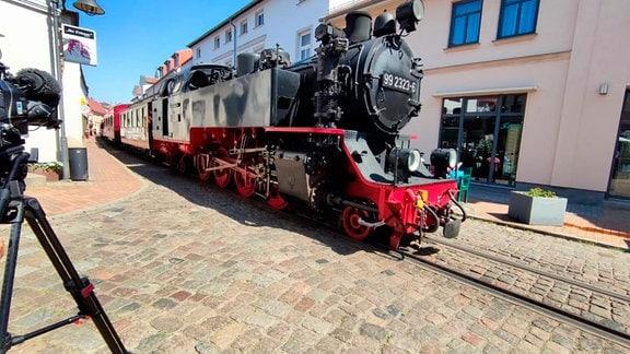 Mollibahn, Kühlungsborn. Eine historisch anmutende schwarze Dampfeisenbahn auf Straßenbahngleisen auf einer gepflasterten Straße in einer Stadt.
