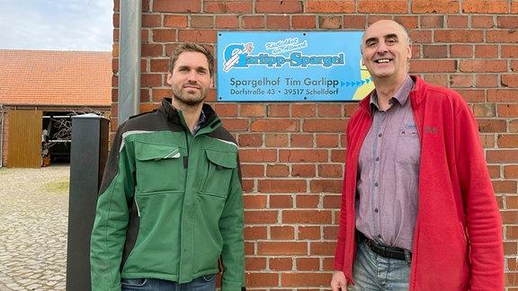 Zwei Personen stehen lächelnd vor einem Schild, das den Spargelverkauf auf dem Hof bewirbt. Im Hintergrund sind Teile eines Bauernhofs zu sehen.