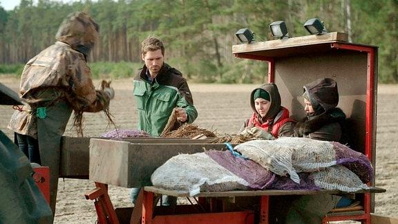 Mehrere Personen auf und an einem landwirtschaftlichen Fahrzeug auf einem Spargelfeld bei der Spargelernte.