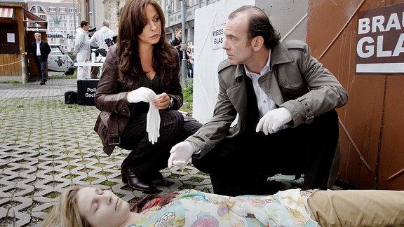 Hauptkommissarin Eva Saalfeld (Simone Thomalla, links) und Hauptkommissar Andreas Keppler (Martin Wuttke, rechts) knien am Tatort vor der ermordeten jungen Frau. Sie ist erschlagen worden.