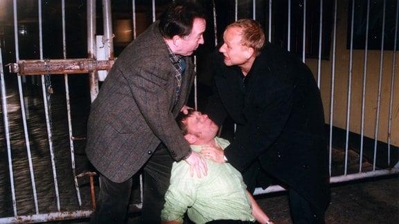 Die Kommissare Ehrlicher (Peter Sodann) und Kain (Bernd-Michael Lade) stellen Roger (Rainer Winkelvoss) nachts auf einem Hinterhof