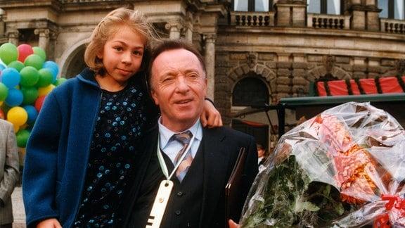 Ehrlicher (Peter Sodann) mit Lina (Romina Penkalla), er hält einen Blumenstrauß in der Hand