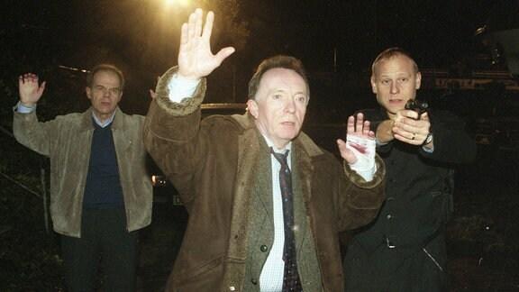 Drei Männer blicken erschrocken in die Kamera und halten die Hände über ihre Köpfe