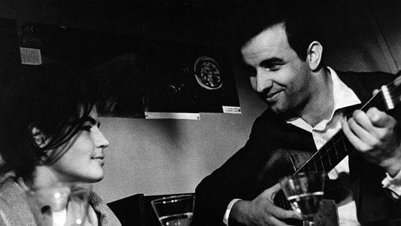 Ein Mann spielt Gitarre und lächelt dabei eine Frau an, die neben ihm sitzt und ebenfalls lächelt.
