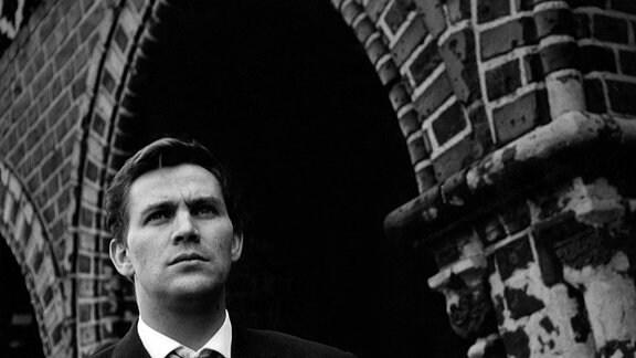 Ein Mann mit sorgenvollem Blick steht vor der Oberbaumbrücke.
