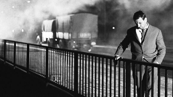 Ein Mann steht an dem Geländer einer Brücke und schaut herunter.