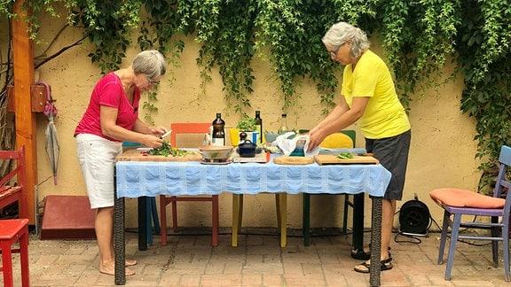 Zwei Frauen stehen sich an einem Tisch gegenüber und zerkleinern Gemüse.