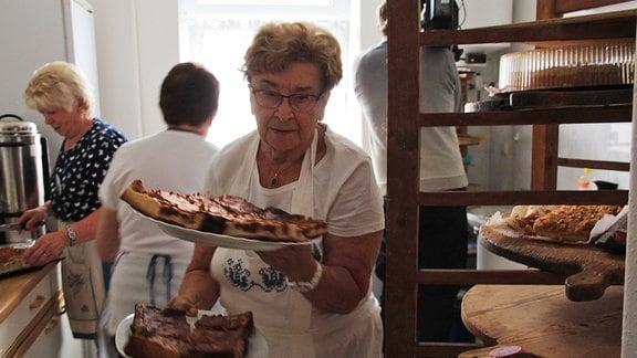 Eine Frau serviert Kuchen