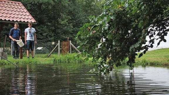 Zwei Männer stehen an einem Teich