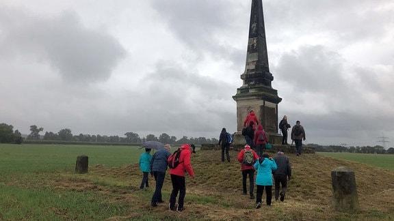 Eine Wandergruppe vor dem Obelisk in Streumen