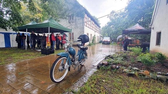 Eine Gruppe Menschen sucht unter einem Pavillon Schutz vor dem Regen. Im Vordergrund steht ein Fahrrad auf einem nassen Weg.