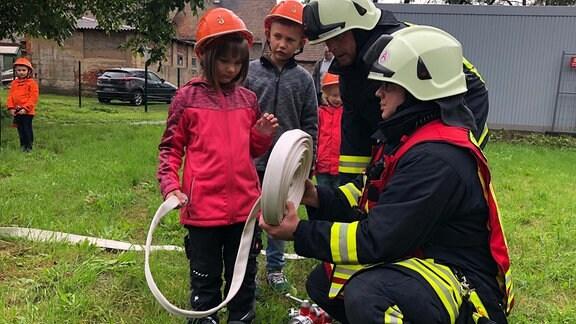 Zwei Kameraden der Freiwilligen Feuerwehr erklären zwei Kindern den Feuerwehreinsatz.